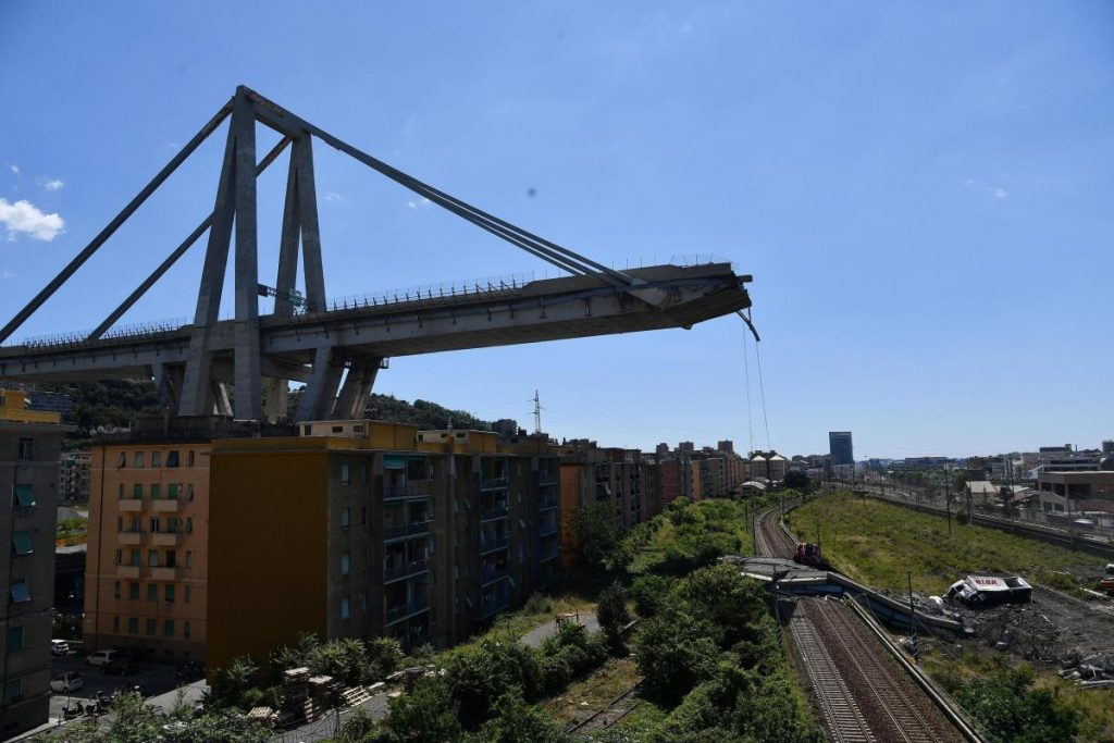 Evacuated housing is visible Wednesday under the remains of the collapsed Morandi highway bridge in Genoa, Italy.