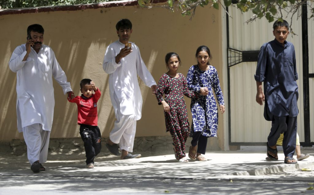 Families leave their homes Thursday in Kabul, where two gunmen engaged police in a six-hourlong standoff at an Afghan intelligence service compound before the security forces killed them. The violence followed Wednesday's killing of 34 youths.