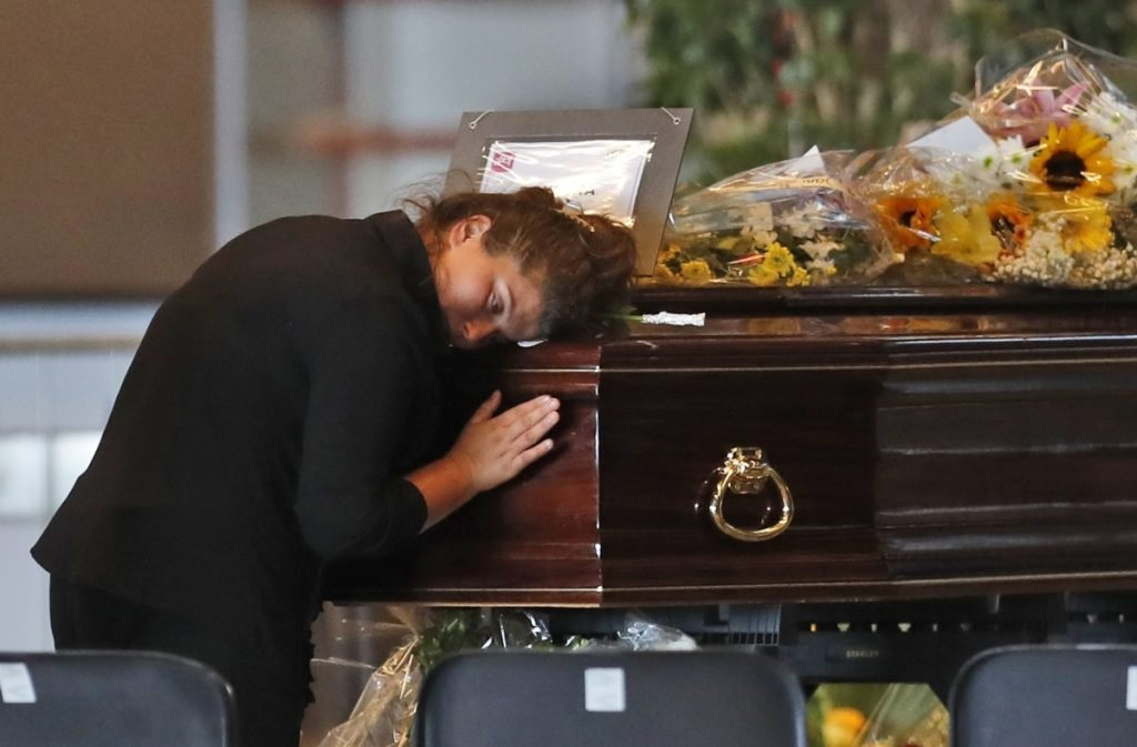 A woman mourns a victim of the collapsed highway bridge Friday at the Fiera di Genova exhibition center, where some of the coffins are laid in state in Genoa, Italy.
