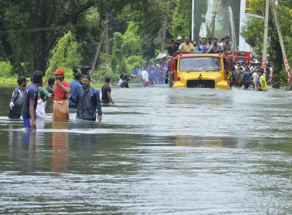 A truck carries people past a flooded road in Thrissur, in the southern Indian state of Kerala, on Saturday. Rescuers used helicopters and boats Friday to evacuate thousands of people stranded on their rooftops from the  flooding.
