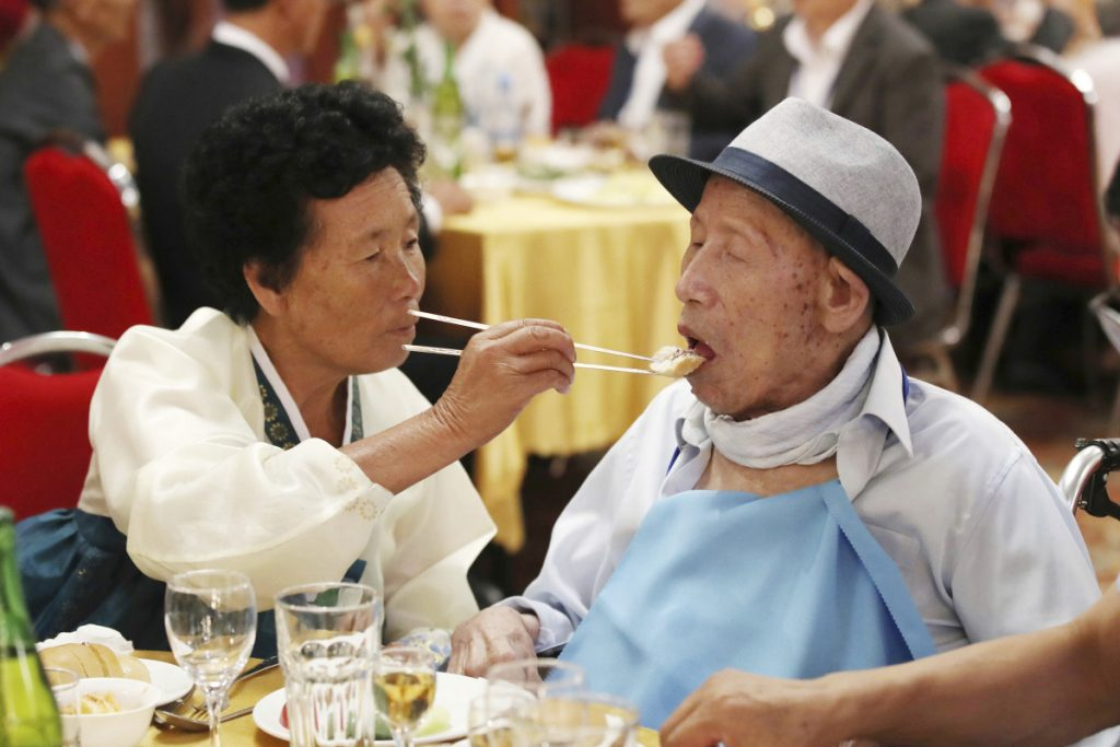 North Korean Ahn Jong Sun, 70, left, feeds her South Korean father Ahn Jong-ho, 100, during a dinner at the Diamond Mountain resort in North Korea on Monday. Dozens of elderly South Koreans crossed the heavily fortified border into North Korea on Monday for heart-wrenching meetings with relatives most haven't seen since they were separated by the turmoil of the Korean War.