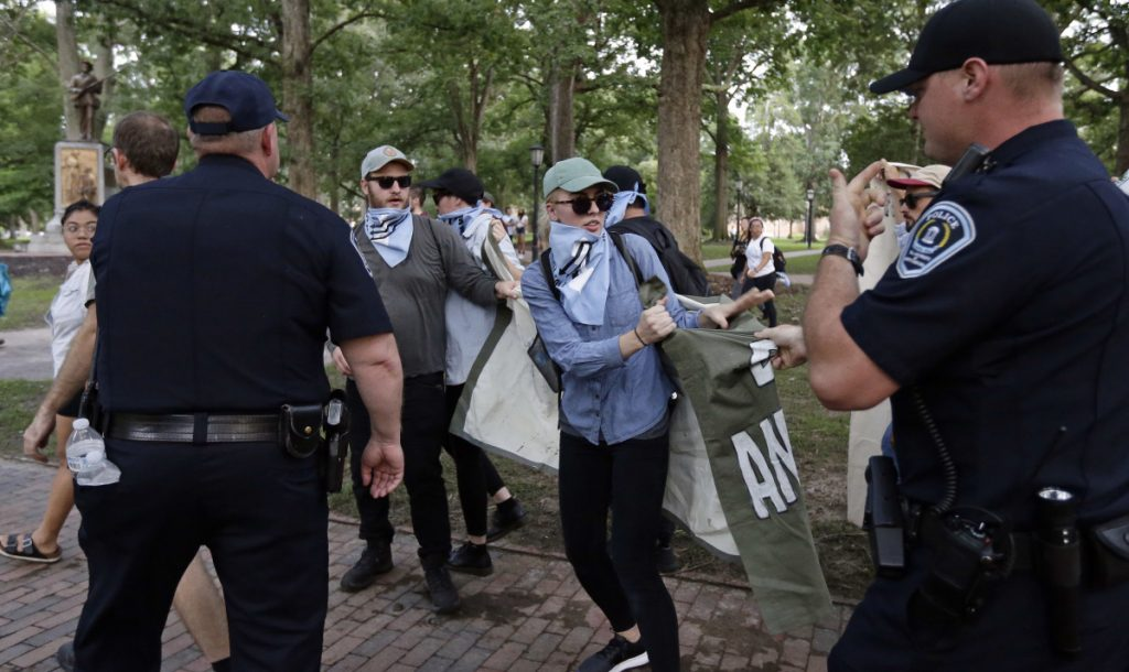 Police try to take a banner from protesters as people gather during a rally to remove the confederate statue known as Silent Sam.