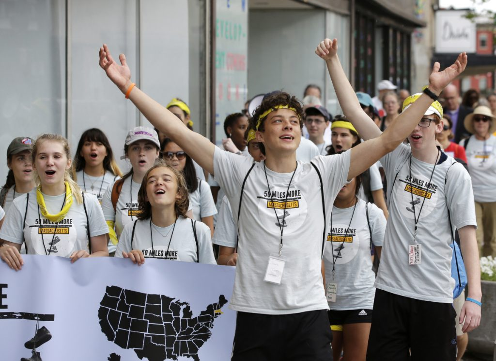 Jack Torres, 16, a Somerville, Mass., high school student, raises his arms while walking in a planned 50-mile march, Thursday in Worcester, Mass. The march, held to call for gun law reforms, began Thursday in Worcester and is scheduled to end Sunday in Springfield, Mass., at the headquarters of gun manufacturer Smith & Wesson.