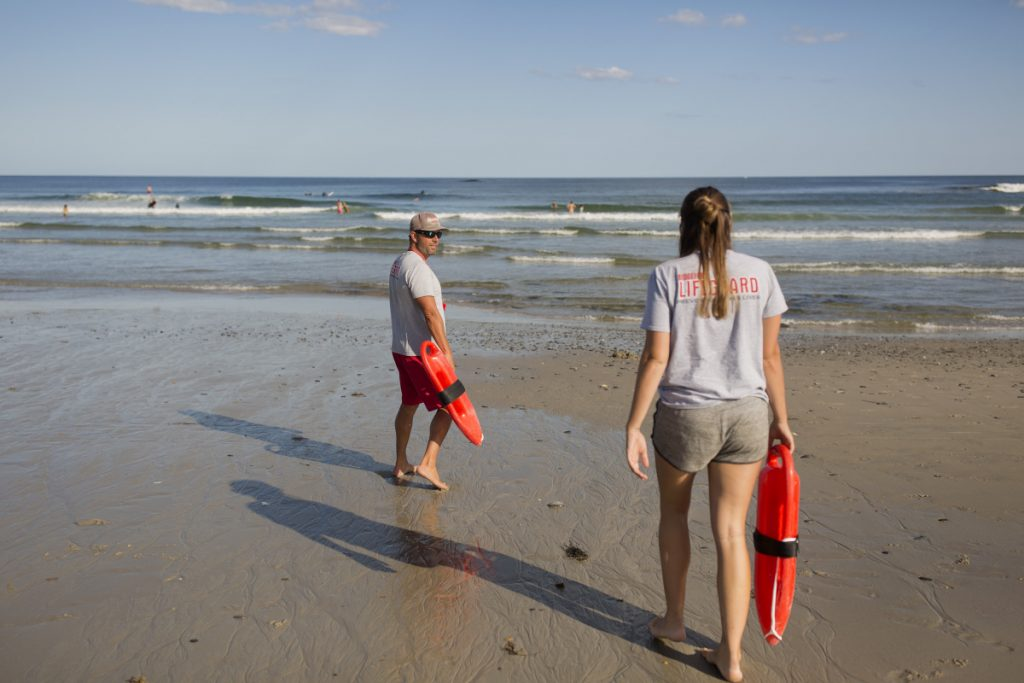 Lifeguard captain Christopher Lessard and lifeguard Mira Kuni walk down to the water at Fortunes Rocks Beach in Biddeford on Thursday.