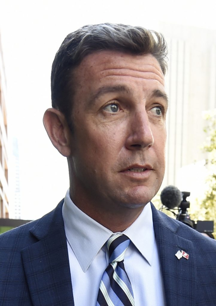 Protesters chant slogans as U.S. Rep. Duncan Hunter arrives for an arraignment hearing Thursday in San Diego. Hunter and his wife were indicted Tuesday.