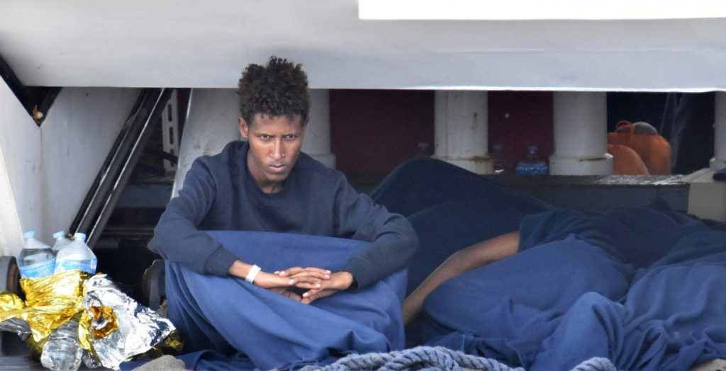 One of about 150 migrants waits aboard the Italian Coast Guard ship Diciotti moored in Catania, Italy, on Wednesday. The migrants are caught up in a dispute between Italy and other European Union nations.