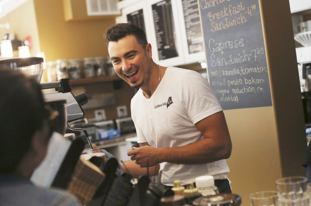 "Mateo Hodo, owner of Coffee Me Up in Portland, makes lattes Sunday. ""Diversity is the key to the economy,"" says the immigrant from Albania."
