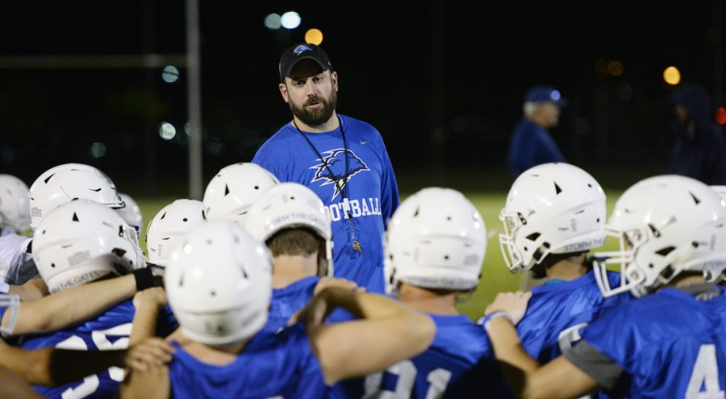 UNE Coach Mike Lichten speaks with his team after its first practice of the season in Biddeford on Aug. 9. At least eight starters played high school football in Maine.