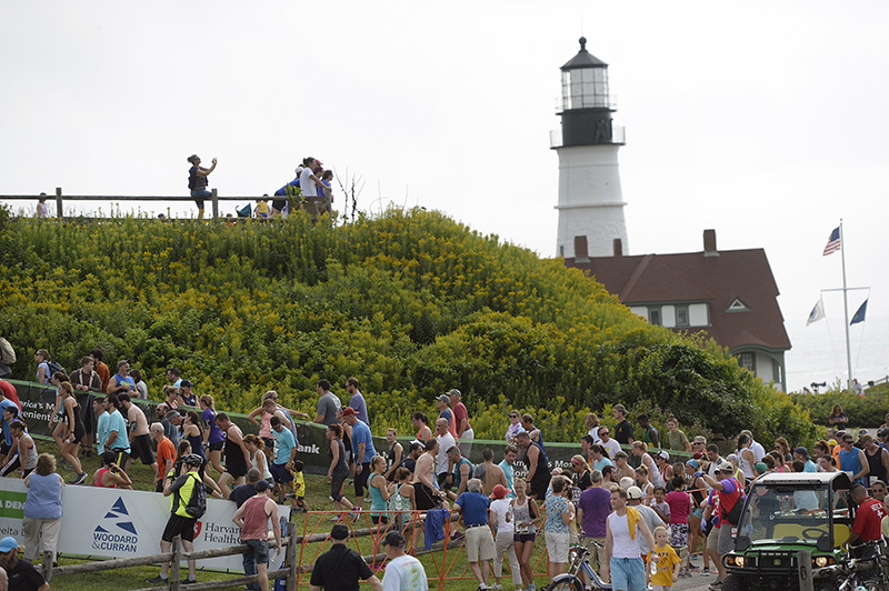 Spectators watch as runners finish the Beach to Beacon near Portland Head Light at Ft. Williams.