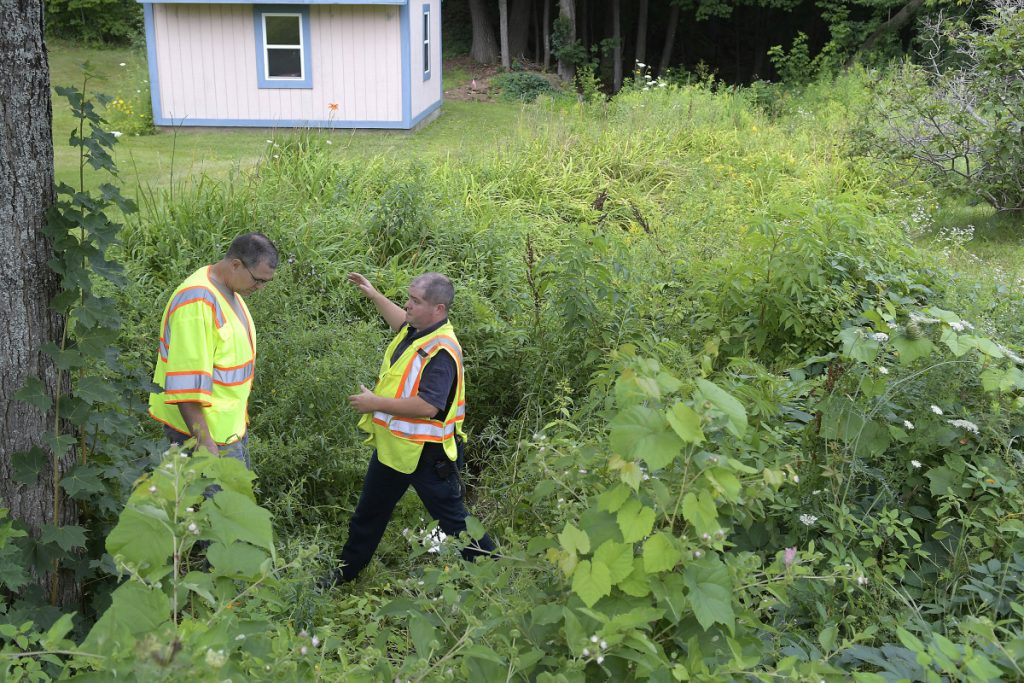 Augusta fire Lt. Brian Chamberlain, right, confers Wednesday with Maine DEP hazardous spill technician Jon Woodard in a small stream where the agencies investigated a heating oil spill.