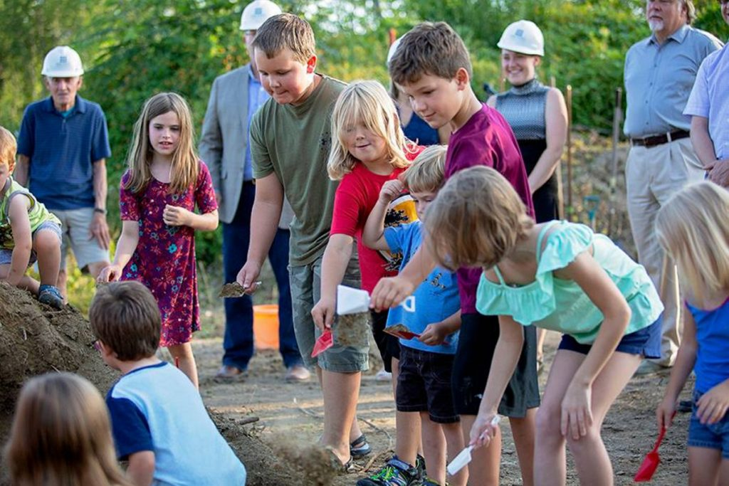 Monmouth students help break ground on the town's new middle-elementary school on the evening of July 31. The school, which is expected to open in January 2020, is being mostly funded by the state.