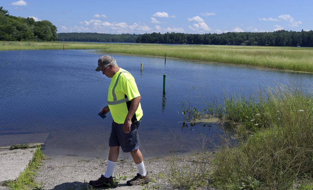 Monmouth Public Works Director Bruce Balfour on Thursday walks along the boat launch on Annabessacook Lake on Waugan Road in Monmouth. Town selectmen have voted to close the boat ramp temporarily because of the presence there of variable-leaf milfoil, pending a legal consultation.