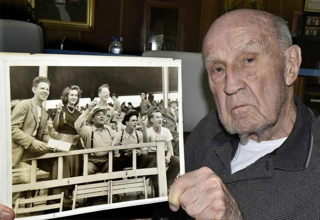 Donald Eames, 91, of Norridgewock, holds a black-and-white photograph Tuesday that shows him cheering during a horse race in the mid-1930s at the Skowhegan Fairgrounds. Eames, who has volunteered for 80 years at the fair, is at bottom right in photo.