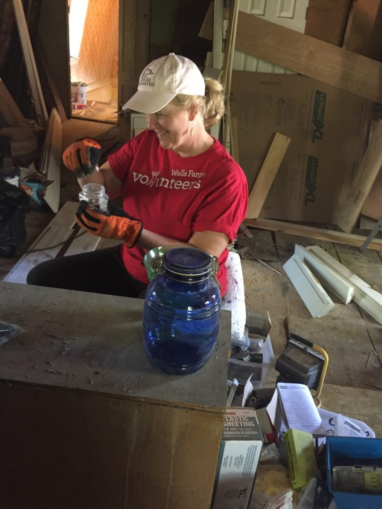 Katy Wood, a strategy consultant from Wells Fargo Community Banking, helps clean up the third floor of the Betsy Ann Ross House of Hope on July 19 in Augusta .