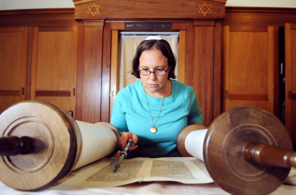Rabbi Erica Asch checks her position in the text as she rolls a Torah scroll in September 2014 in preparation for Rosh Hashanah services at Temple Beth El in Augusta. She is leading a local group seeking Augusta to add major religious holidays for multiple religions, including Jewish and Muslim holidays, to school calendars. The Augusta Board of Education's Policy Committee will discuss the proposal Monday.