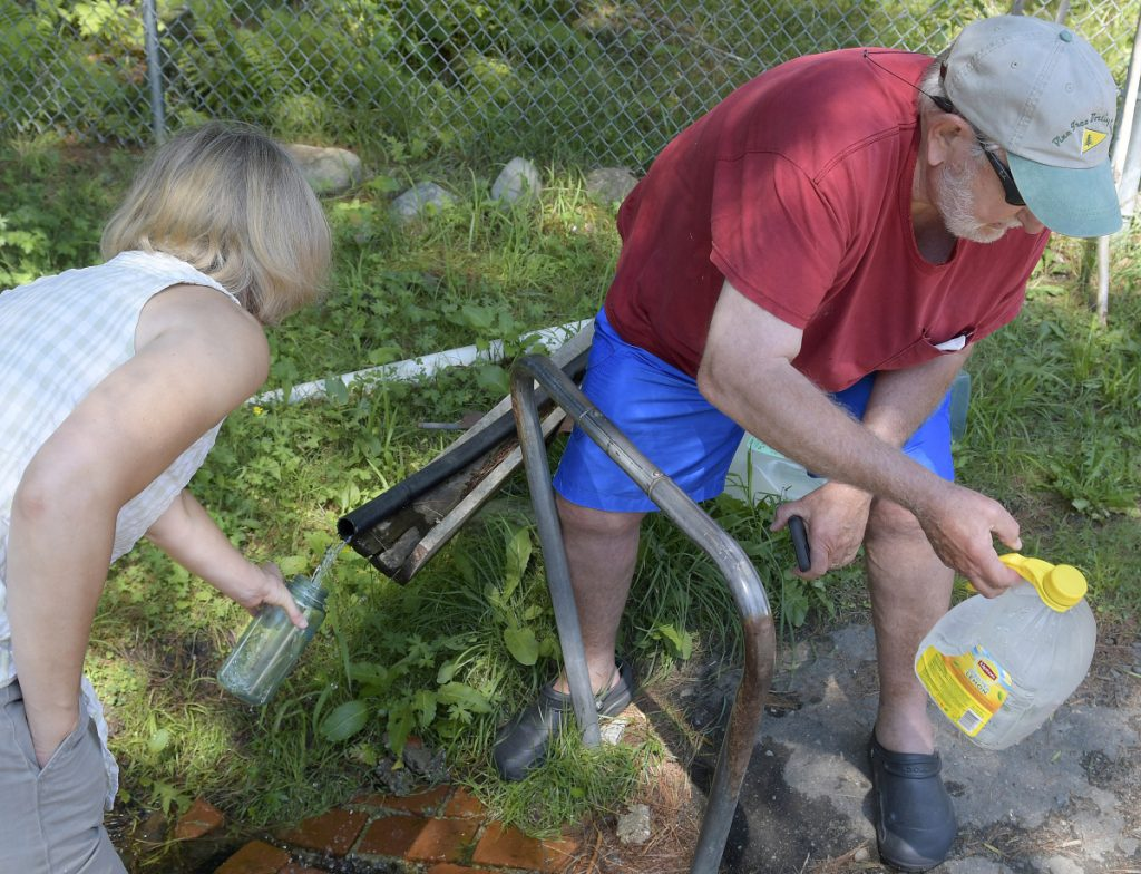 Deb Wachter and Wilson Eick fill jugs with water Sunday from the Vienna Village Spring. The summer residents of Vienna replenished their drinking supplies from the aquifer that was opened for public drinking in 1886.