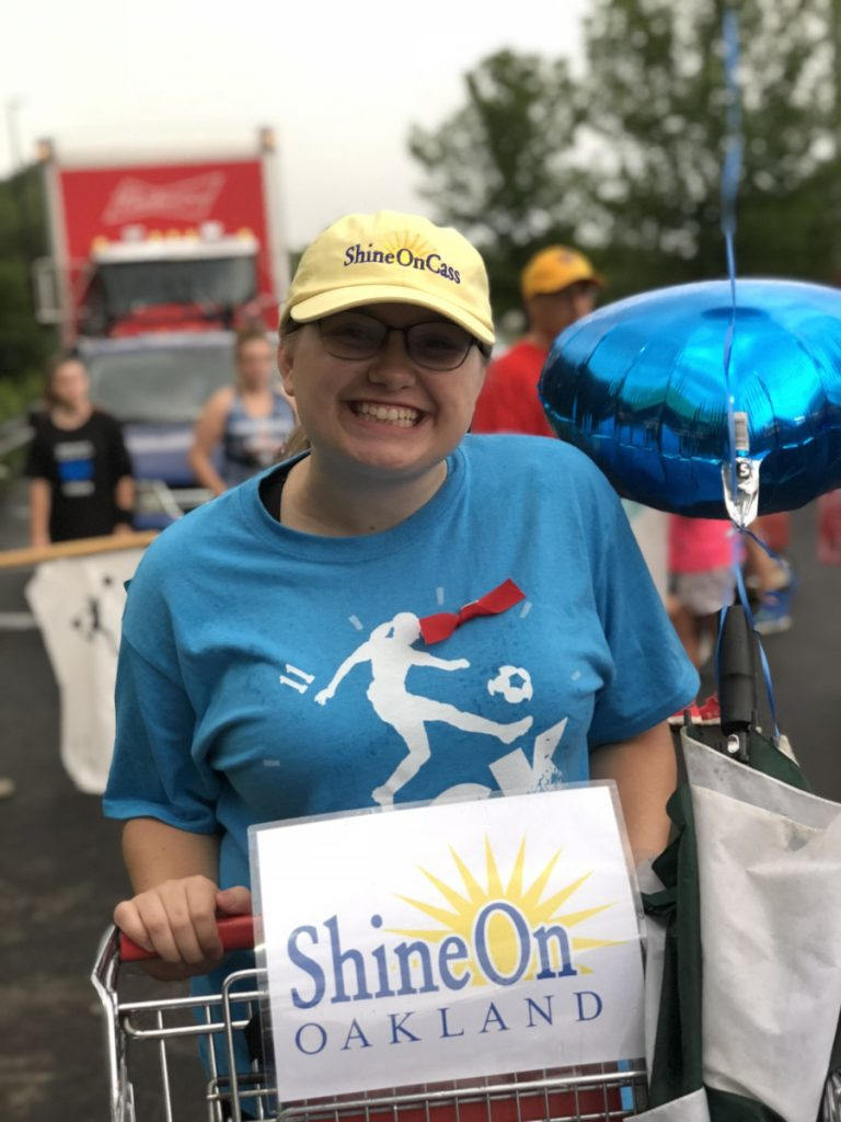Anya Fegal helps collect cereal boxes in one of the ShineOnCass shopping carts in the Oakfest Parade July 27. More than 150 boxes of cereal were donated to help feed local kids this summer. The event was organized by the ShineOnCass Foundation.