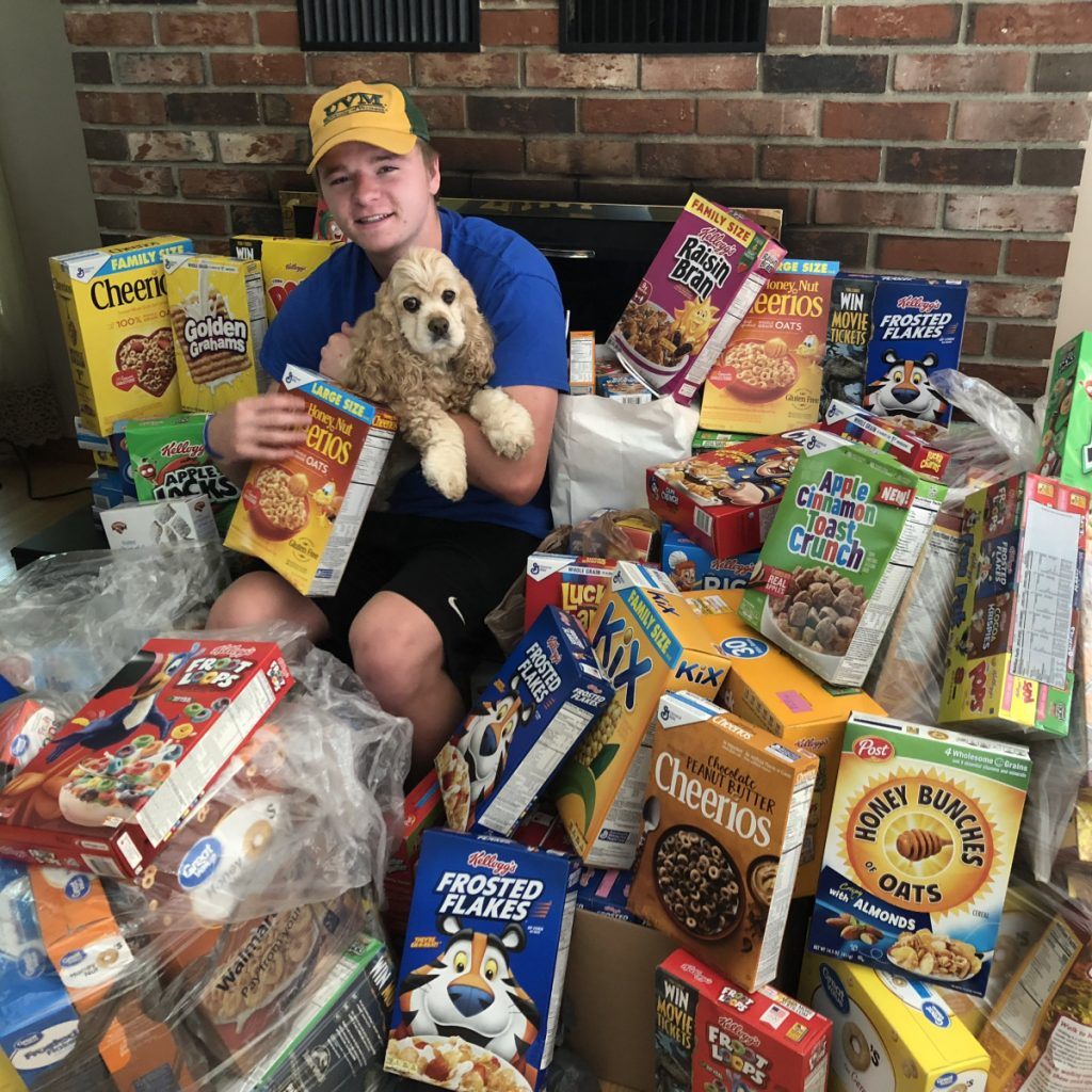 Colby Charette and his dog Sadie sit among the more than150 boxes of cereal collected at Oakfest's first ShineOn Oakland Day in support of local kids. The cereal drive was organized by the ShineOnCass Foundation to support local families through the Oakland Food Pantry.