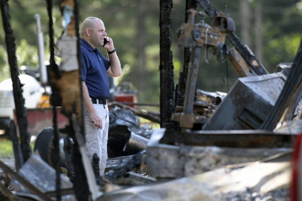 A investigator with the Office of State Fire Marshal on Wednesday examines a residence destroyed by fire on Hunts Meadow Road in Whitefield.