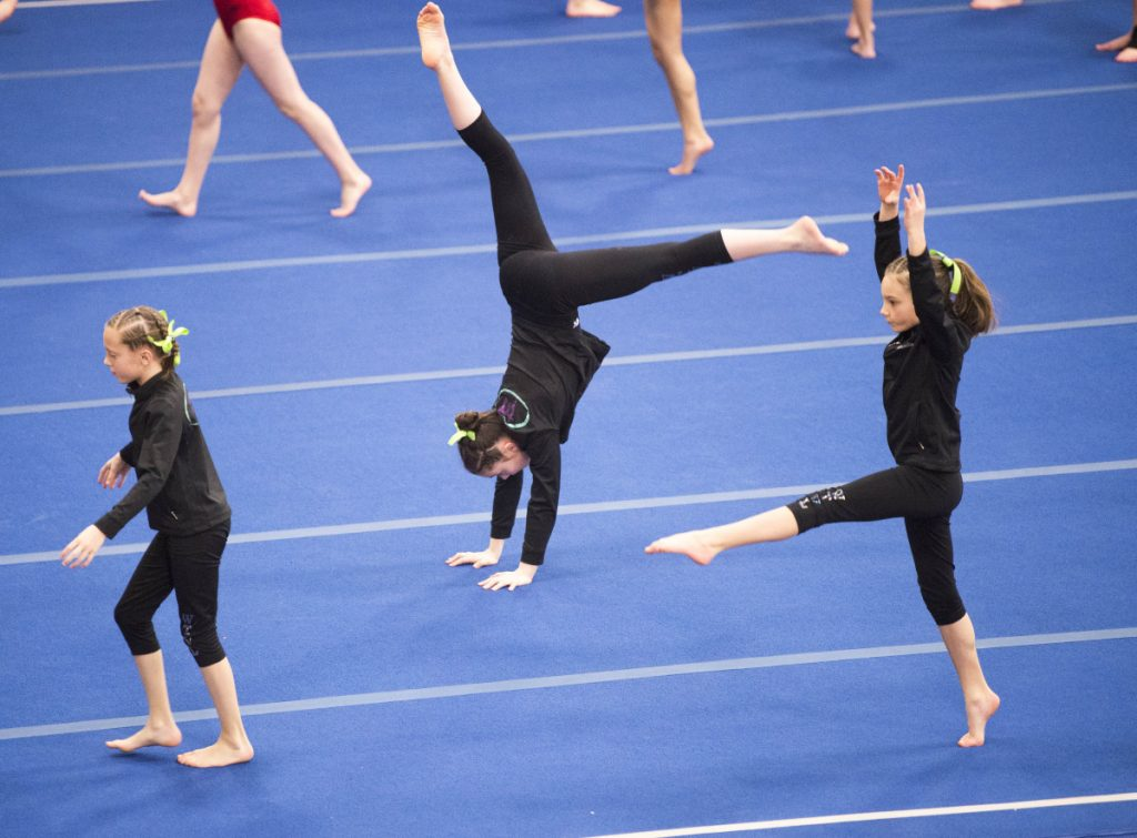 Gymnasts from Decal Gymnastics warm up during a meet at the Alfond Youth Center in Waterville on April 14, 2018.