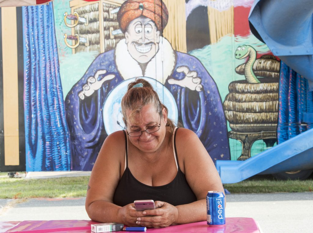 Gayle Palombo, a worker with Fiesta Shows, takes a break in front of the fun house as crews set up for the 200th annual Skowhegan State Fair at the Skowhegan Fair Grounds on Wednesday.
