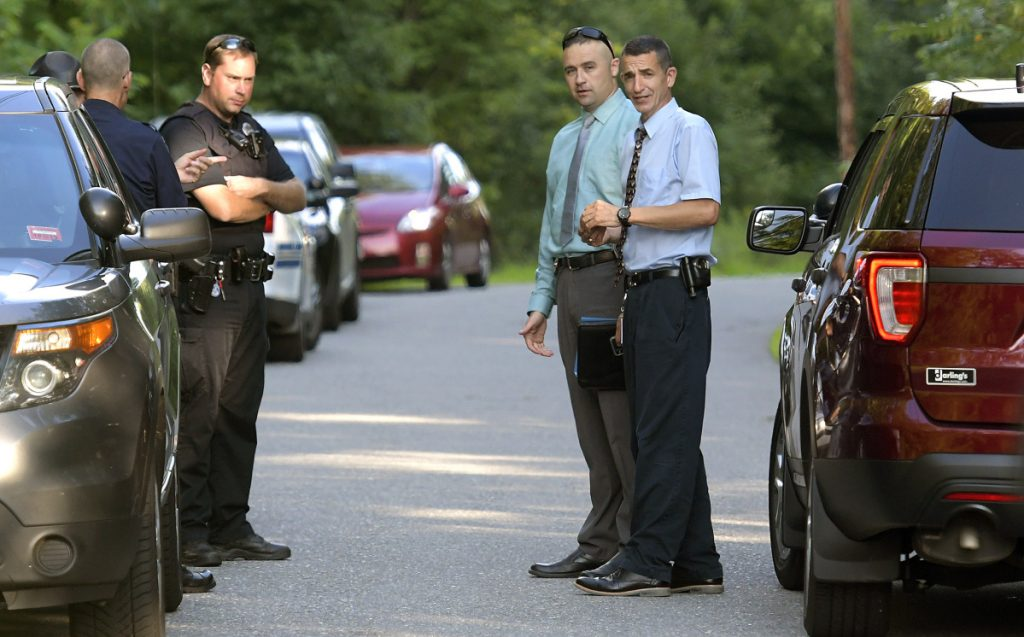 Maine State Police Col. John Cote, right, speaks with officers Thursday evening at an incident involving two deaths on Timberwood Drive in Gardiner.