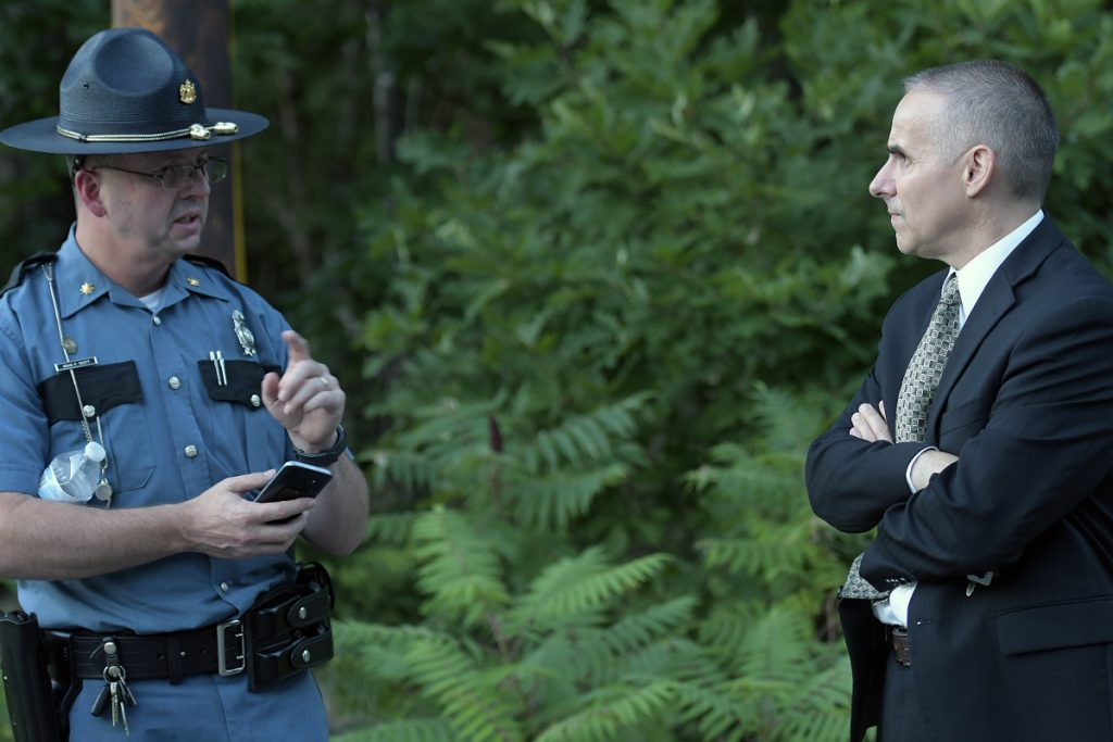 State police Maj. Brian Scott, left, confers Thursday with Lt. Col. William Harwood at the scene where a Massachusetts man, Gyrth Rutan, shot himself to death on Timberwood Drive in Gardiner. A woman's body was found in the trunk of a car Rutan had been driving.