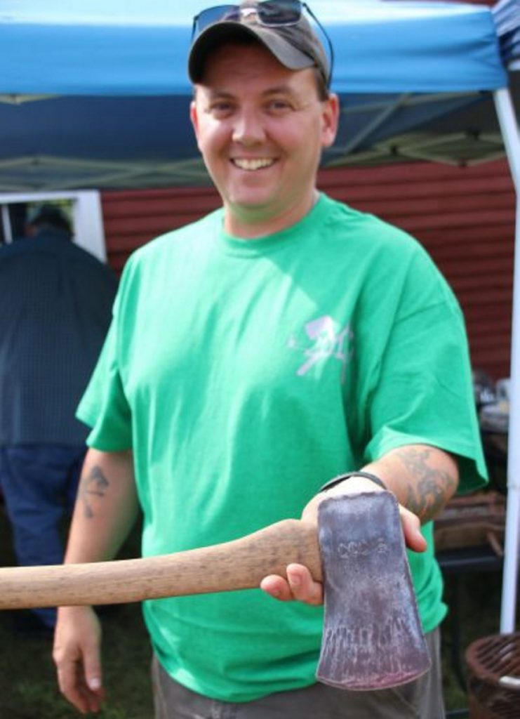 Mike Fraser, of Sanford, an organizer of the Maine Axe & Saw Meet Up that took place in Waterboro on Saturday, displays an axe in his collection inscribed CCC-S, which means it was a Civilian Conservation Corps axe used on a state project. The CCC was established by President Franklin Delano Roosevelt in 1933 to provide work to the unemployed during the Great Depression.