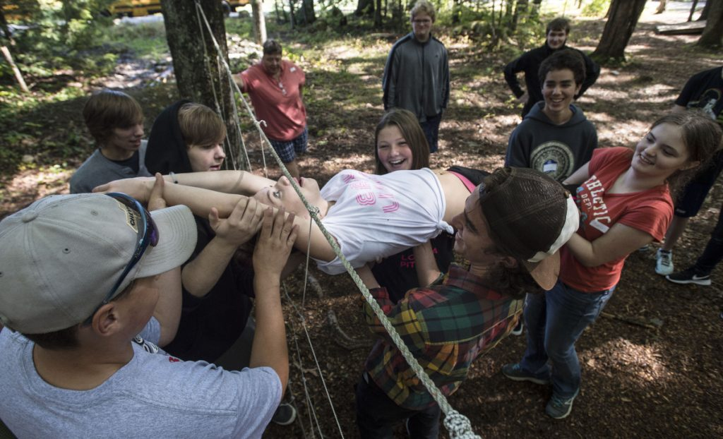 Abby Partridge, a student at MeANS Good-Will Hinckley school, is lifted and passed through the spider web initiative with the help of classmates on Sept. 8, 2017, at Camp Tracy in Oakland.