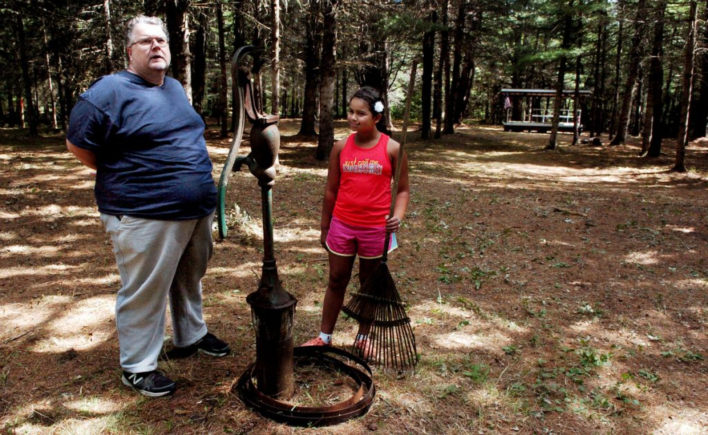 Bill Owen and daughter Jasmine stand beside a spring well located in the woods off the 4 Square Mile Road in North Anson, where performers were scheduled to take the stage, background, for the Billy's Belly Bluegrass and Folk Music competition in August 2016. The festival was canceled this year, but the Wesserunsett Arts Council has come up with an Arts in the Woods competition at Billy's Belly Pavilion on Saturday.