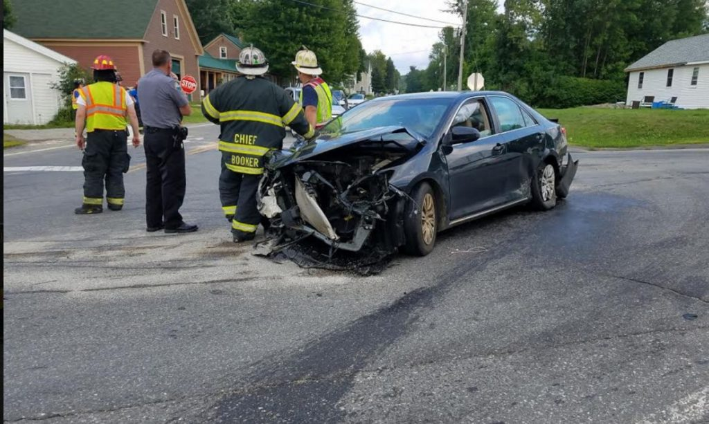Firefighters and a police officer stand next to a car driven by Adelle Foss, 17, of Farmington, who was injured Wednesday afternoon in a three-vehicle collision at routes 133 and 156. She was taken to a local hospital for treatment of minor injuries.