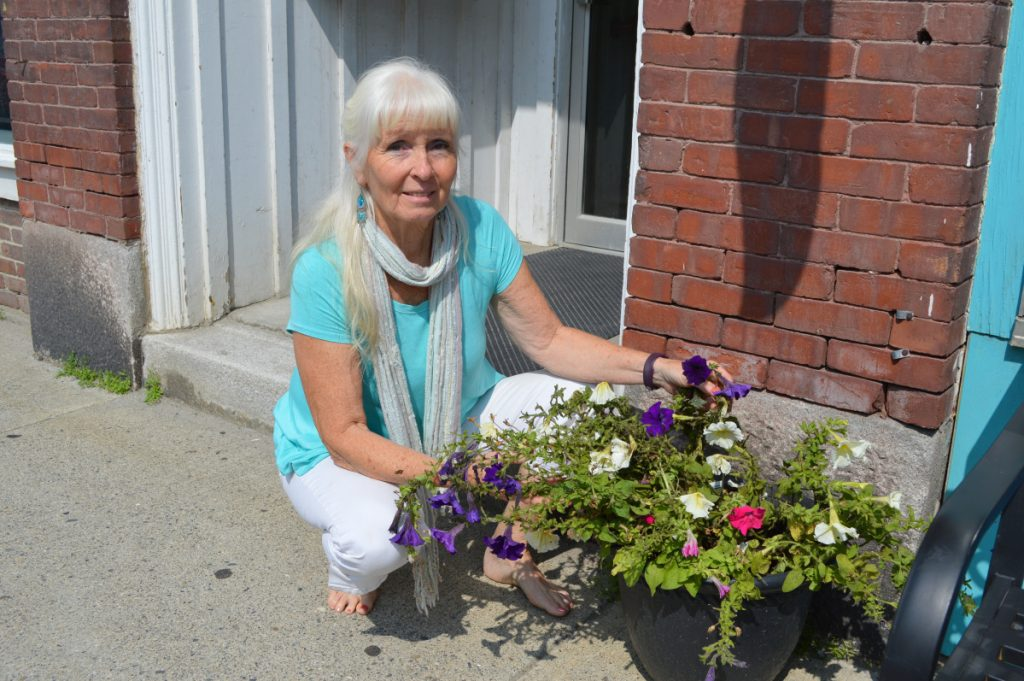 Susun Terese, owner of Minikins on Broadway in Farmington, crouches next to one of her planters on Friday that was tipped over during a vandalism spree that struck the downtown area and the University of Maine at Farmington campus in the early morning hours.