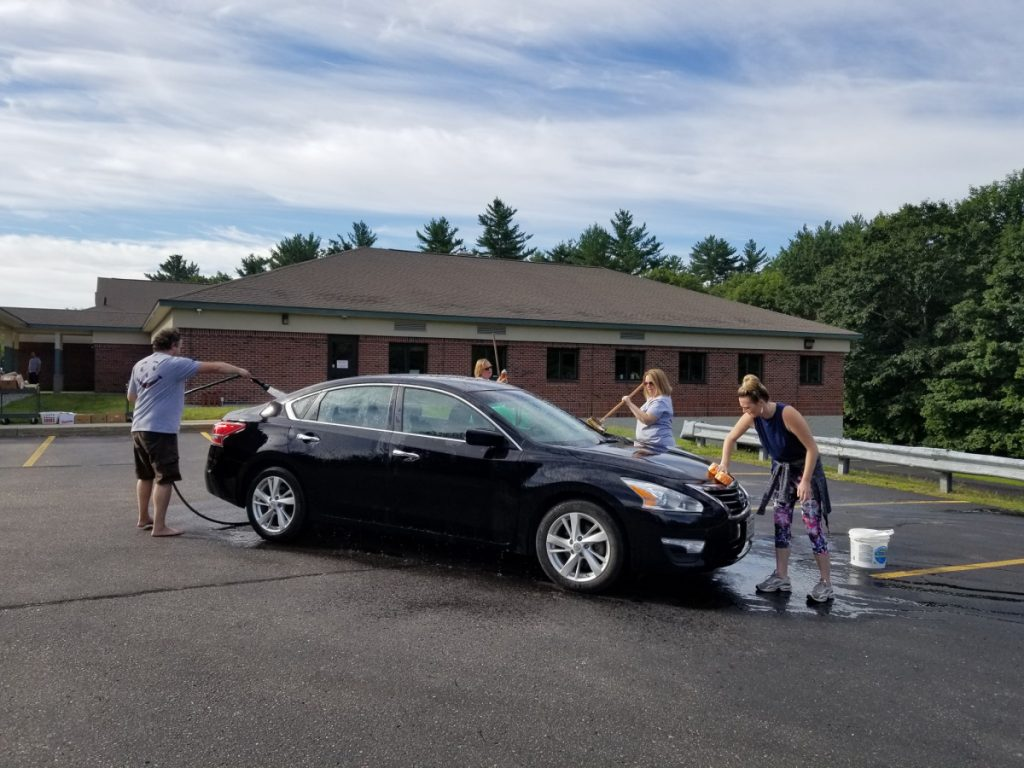 Individuals washing black car from left are Ben Roberts, compliance officer and training specialist; Kim Turner, president/CEO; Stephanie Nichols, cards specialist; and Alicia Fanjoy, teller, all with OTIS Federal Credit Union in Jay.