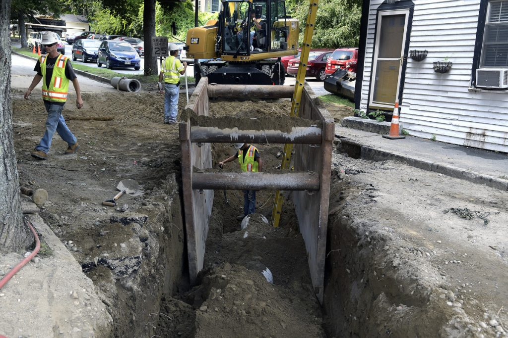 Sargent Corporation workers set a pipe at the intersection of Water and Academy streets in Hallowell Monday as part of the Maine Department of Transportation's reconstruction of Route 201 Project.