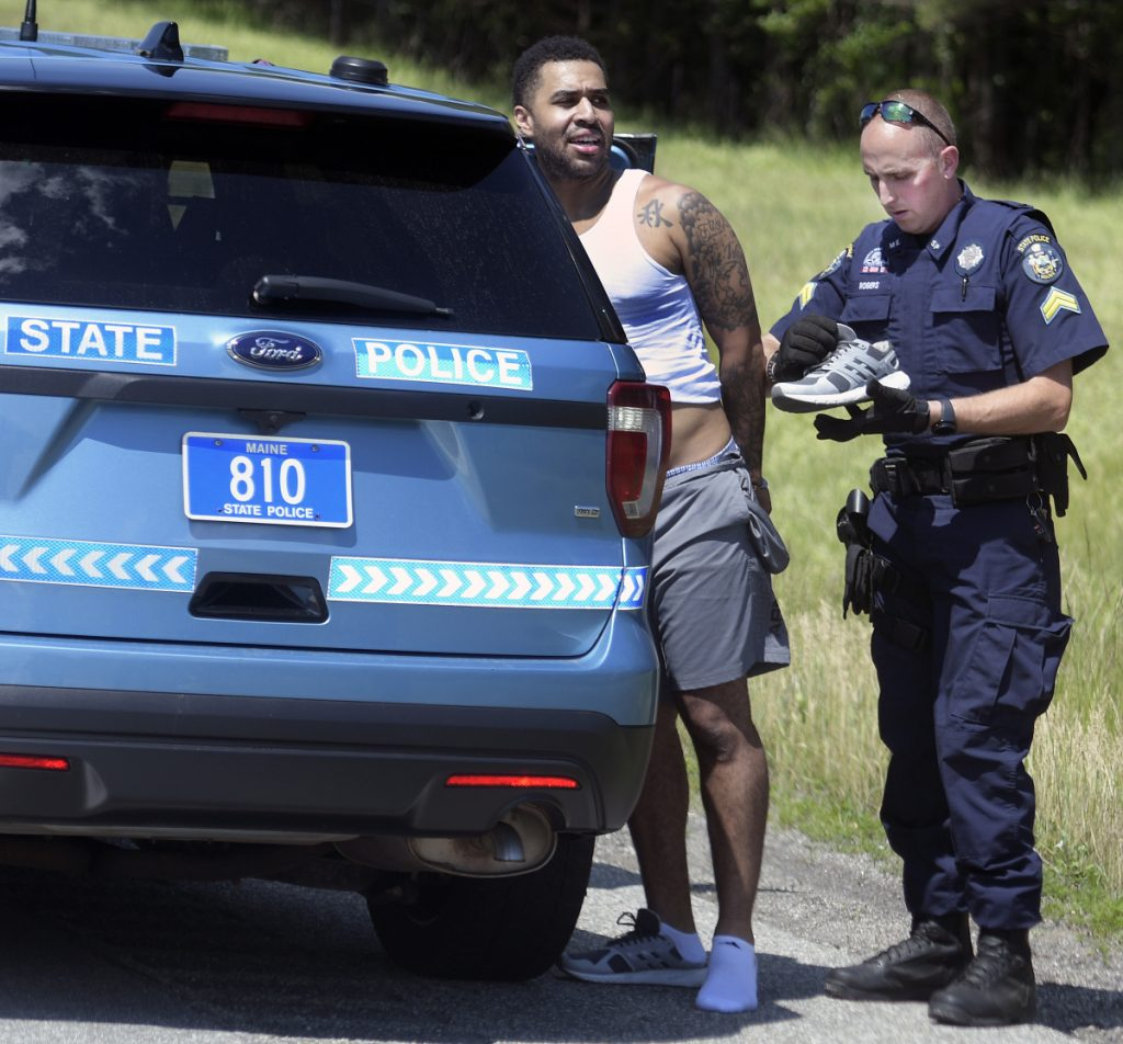 State police Cpl. Chris Rogers examines the clothes of Lenwood Williams, of Baltimore, Maryland, who was arrested June 29 on the Maine Turnpike in the Hallowell and Farmingdale area after a high-speed pursuit.