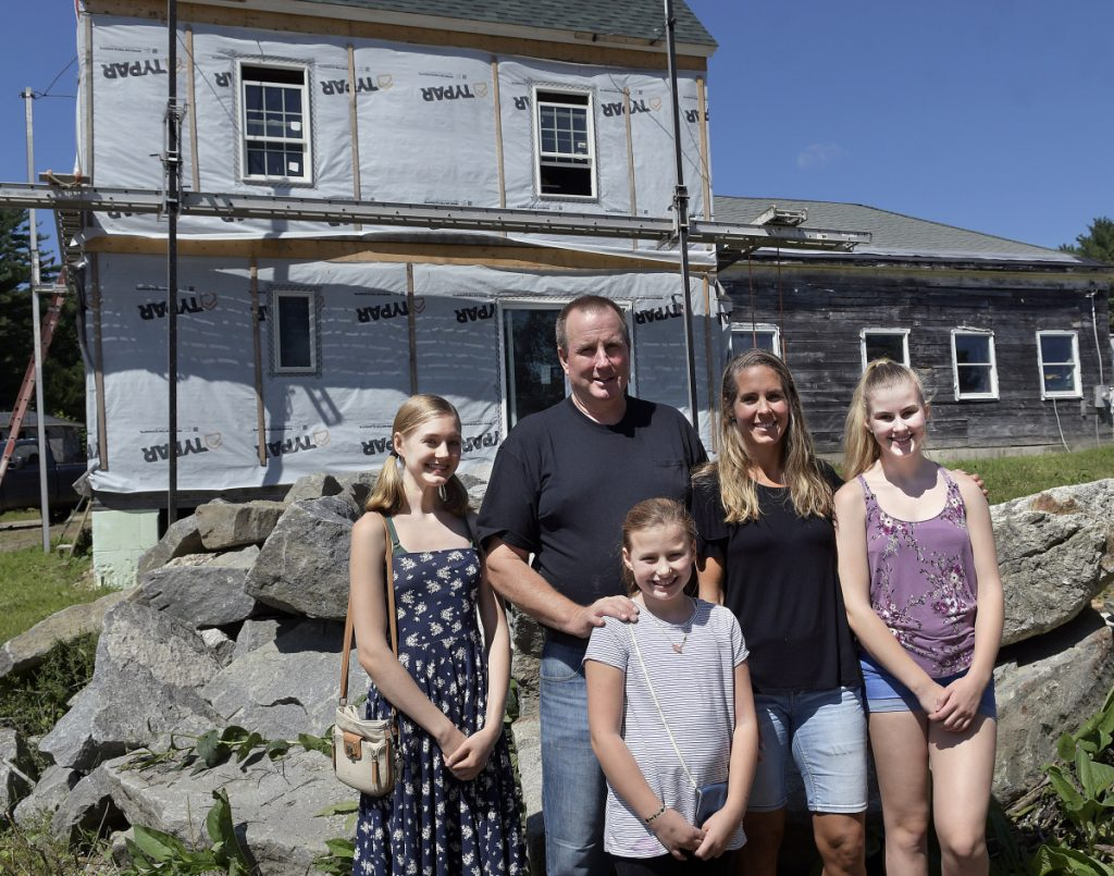 Calista, left, Christina and Shae-Lynn Pagurko with their parents, John and Melanie, are seen outside the home they are rebuilding on Thursday in Whitefield following a destructive fire last year.