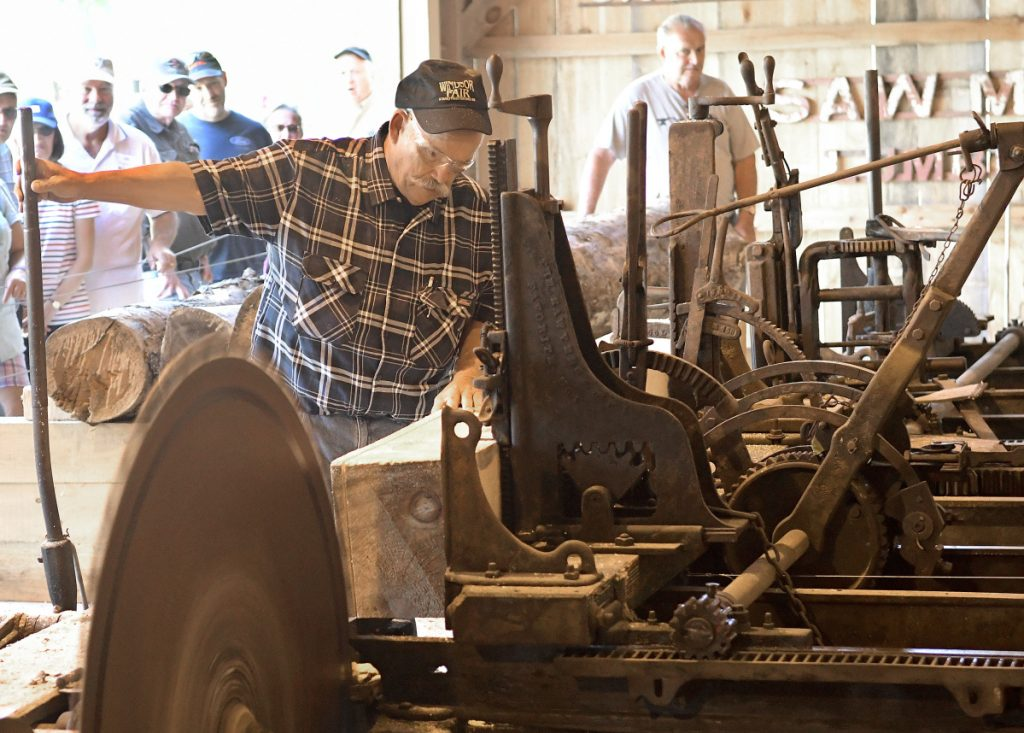 Bob Brown, left, and Jim Hawkes cut a log Sunday at the saw mill recently reassembled at the Windsor Fairgrounds.