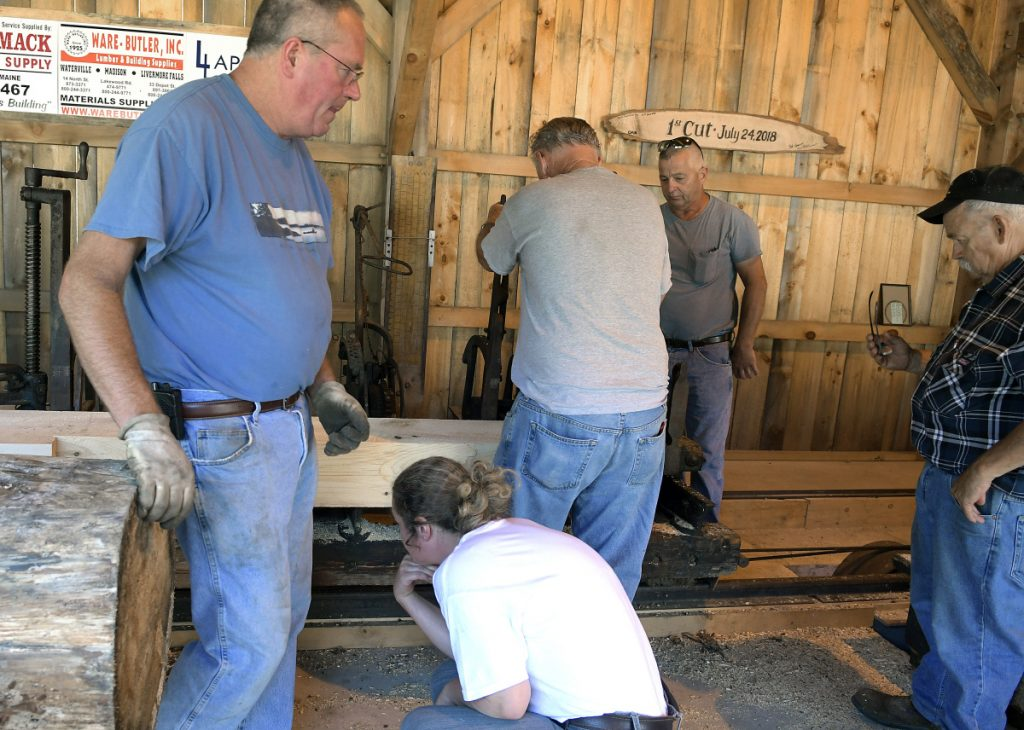 Volunteers attempt to fix the saw mill Sunday at the Windsor Fairgrounds after it malfunctioned.