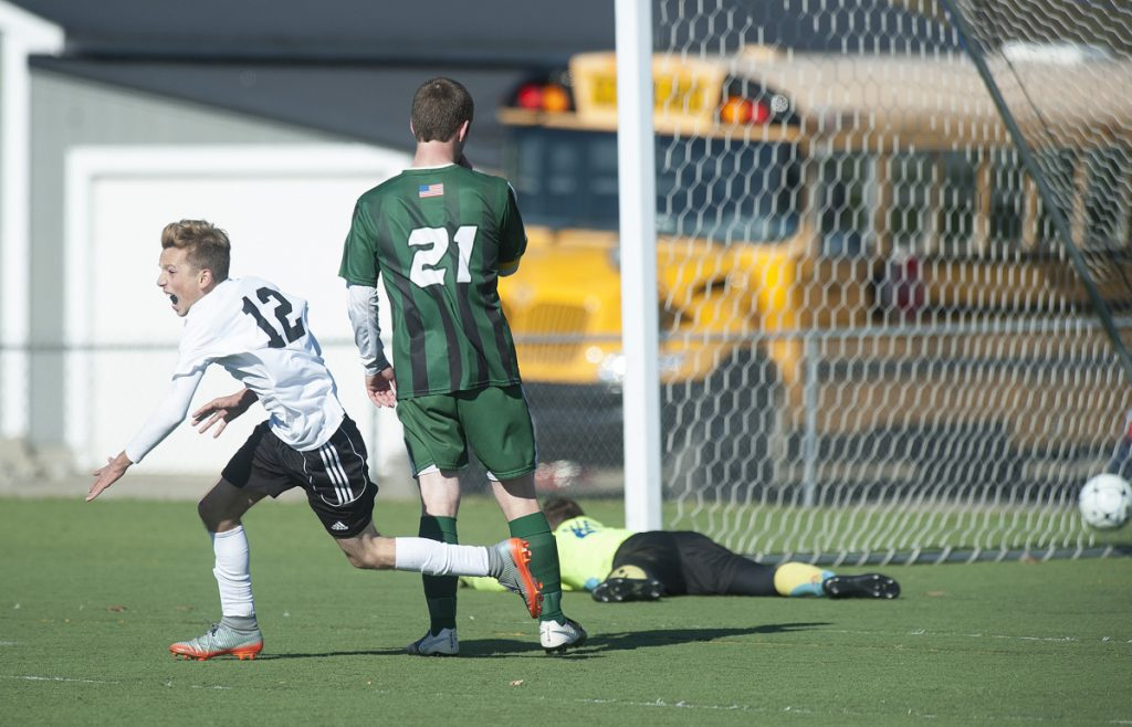 Photo by Kevin Bennett   Late strike: Wyatt Lambert runs to celebrate with his Maranacook boys soccer teammates after Silas Mohlar scored with 20 seconds left in regulation to give the Black Bears a 1-0 victory over Fort Kent in the Class C state title game last season at Hampden Academy.