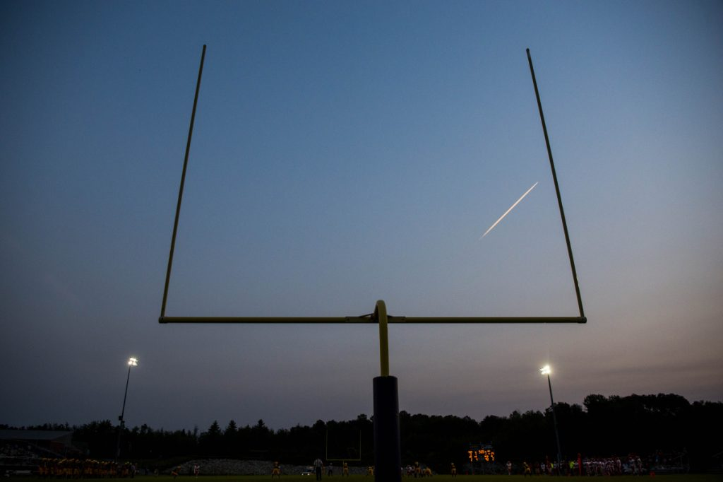 Staff photo by Michael G. Seamans   A jet's vapor trail splits the goal posts at Caldwell Field on the Mt. Blue High School campus in Farmington during an Aug. 24 preseason game betwen the Cougars and Cony Rams.