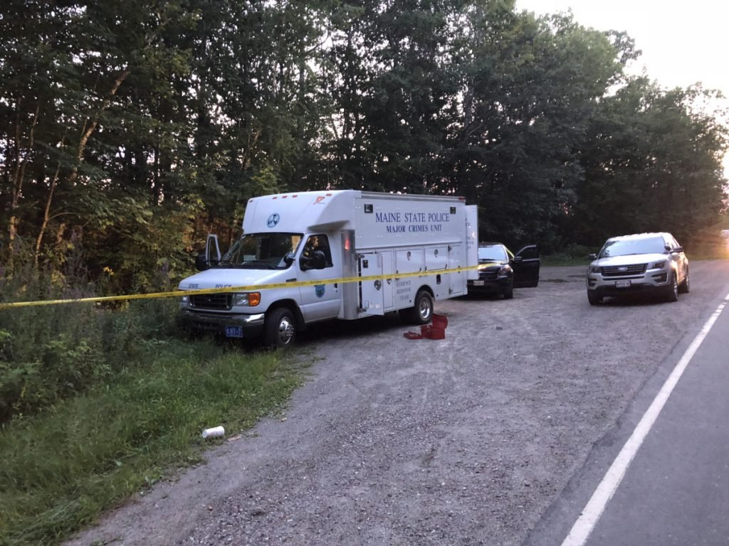 A Maine State Police major crimes van is parked at the side of Weeks Mills Road in Augusta, near where a body was found Aug. 23.