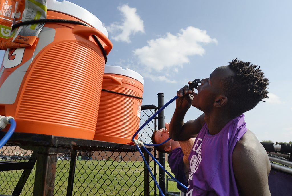 James Opio and Lucas Harbaugh, in background, drink water before the Deering High School football practice Tuesday. With Tuesday's hot weather, the team practiced without pads and took frequent water breaks.