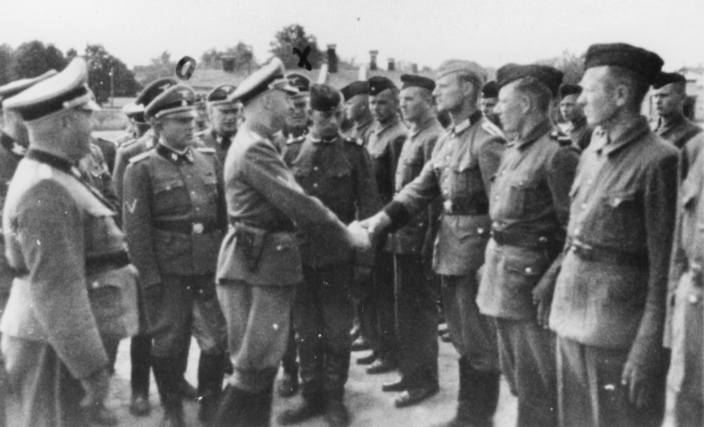 This 1942 photo provided by the the public prosecutor's office in Hamburg via the United States Holocaust Memorial Museum, shows Heinrich Himmler, center left, shaking hands with new guard recruits at the Trawniki concentration camp in Nazi occupied Poland. Trawniki is the same camp, where some time after this photo was made, Jakiw Palij trained and served as a guard.