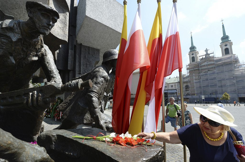 Warsaw residents lay flowers Wednesday at the monument to the 1944 Warsaw Rising against the occupying Nazis to honor some 18,000 resistance fighters who fell in the struggle against the German forces and some 180,000 civilians who perished 74 years ago, in Warsaw, Poland.
