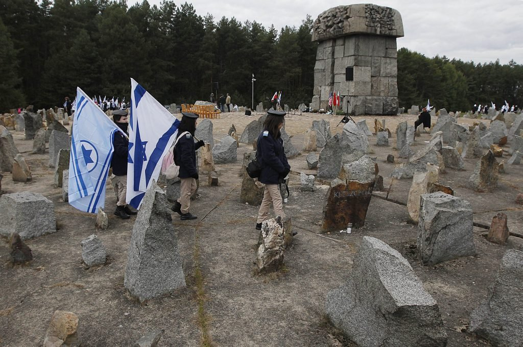 Israeli youths with national flags march in 2013 by the monument to some 900,000 European Jews killed by the Nazis between 1941 and 1944 at the Treblinka death and labor camp, at Treblinka memorial, Poland.