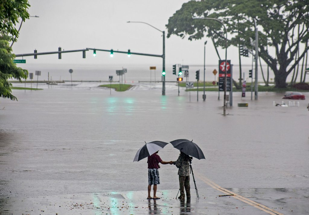 People stand near flood waters from Hurricane Lane on Thursday in Hilo, Hawaii. The storm dumped nearly 20 inches of rain in 24 hours as residents stocked up on supplies and tried to protect their homes from the state's first hurricane since 1992.