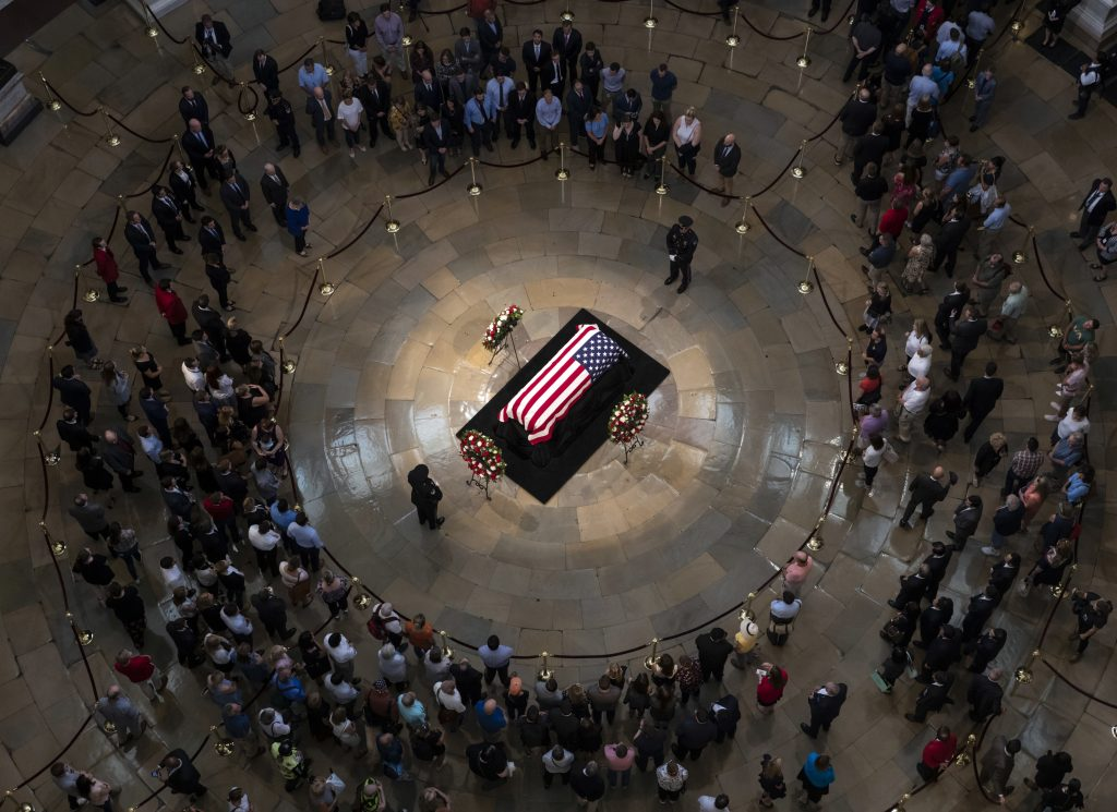 Members of the public walk past the flag-draped casket bearing the remains of John McCain of Arizona, who lived and worked in Congress over four decades, in the U.S. Capitol rotunda in Washington, Friday, Aug. 31, 2018. McCain was a six-term senator from Arizona, a former Republican nominee for president, and a Navy pilot who served in Vietnam where he endured five-and-a-half years as a prisoner of war.