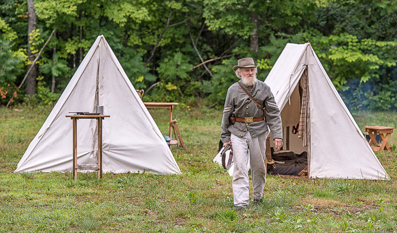 Tom Bassford, a civil war reenactor, walks away from his tent during the second  annual Civil War Encampment.