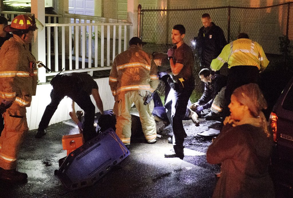 Rescue personnel tend to two people who fell from a third-story porch on Pierce Street in Lewiston on Wednesday night.