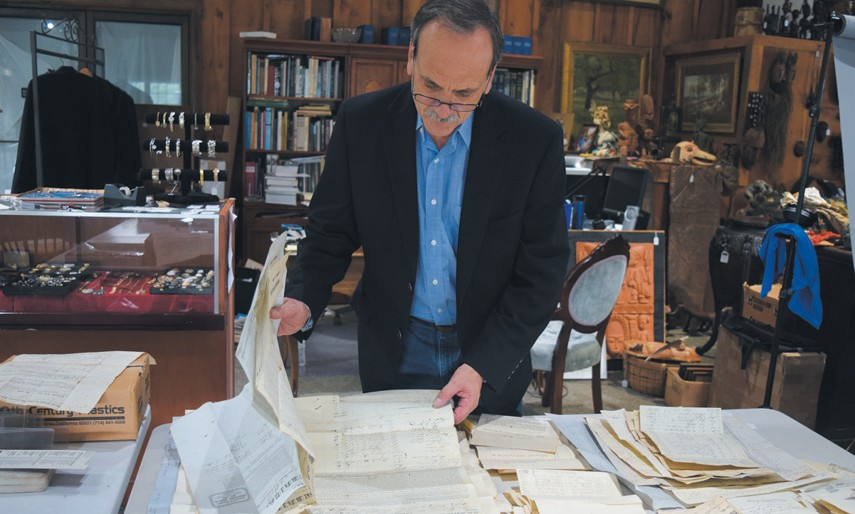 Daniel Buck Soules examines documents related to Crooker shipping at his auction house in Lisbon Falls.
